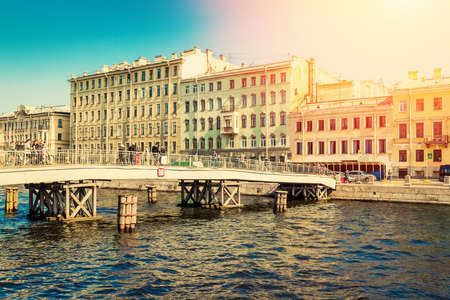 View of historic houses and bridge across Fontanka canal in Saint Petersburg, Russia.