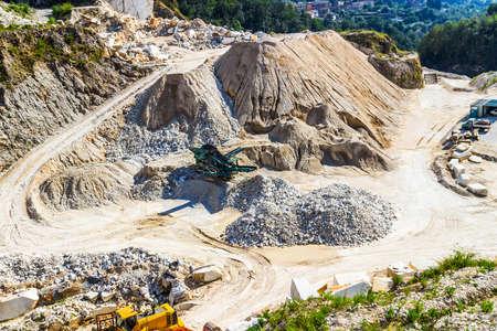 Excavator machine works with marble blocks in Carrara, Massa-Carrara, Italy.