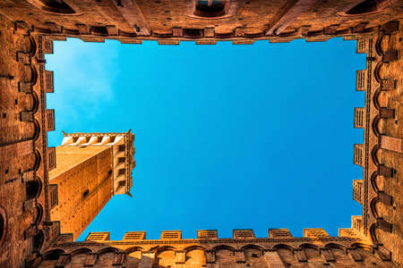 Famous Torre del Mangia tower over blue sky in Siena, Tuscany, Italy.