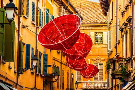 reggio emilia: Red umbrellas hanging on old street in Reggio Emilia, Italy.