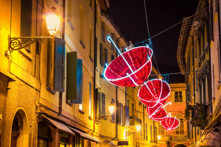 Red umbrellas decorates night street in old town in Italy.