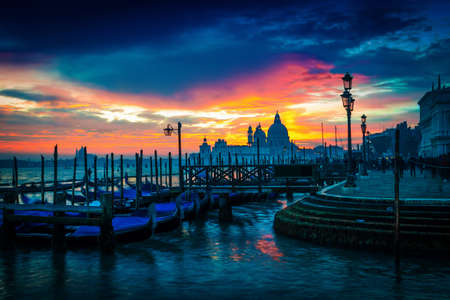 Scenic sunset in Venice, Italy. View of gondolas and Santa Maria cathedral.