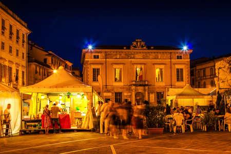 People eating traditional Italian dishes in Sarzana, Liguria, Italy. Summer food festival.