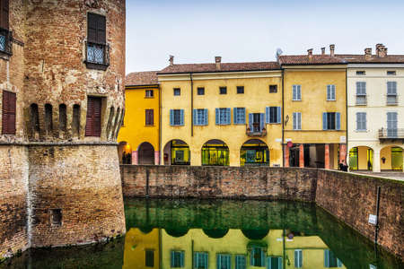 Colorful old houses along the fosse of the castle in Fontanellato, Emilia-Romagna, Italy. Editorial