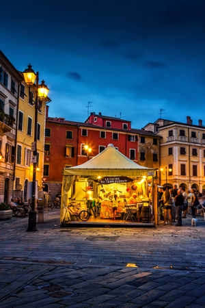 SARZANA, ITALY - AUGUST 10, 2015: People buying traditional Italian cuisine food on the square - Piazza Giacomo Matteotti in Sarzana, Italy. Summer food festival. Editorial