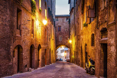 Night old streets in medieval Siena, Tuscany region, Italy.