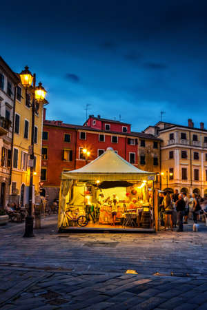 People buying traditional Italian cuisine food on the square - Piazza Giacomo Matteotti in Sarzana, Italy.