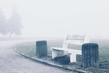 Bench in misty park. Stock Photo