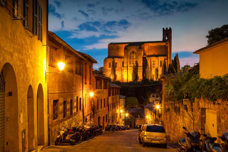 Night old street and view of San Domenico Cathedral in Siena, Tuscany, Italy. Stock Photo