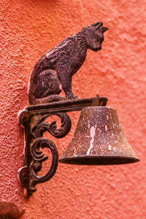 Metal cat decoration on the house wall.