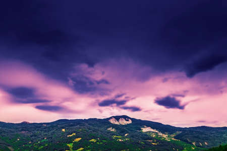 Dark sunset clouds above the mountain.