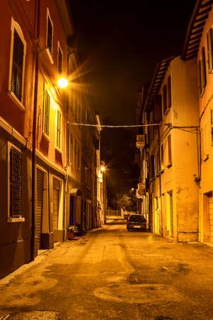 Narrow old night street in Reggio Emilia, Emilia-Romagna, Italy.