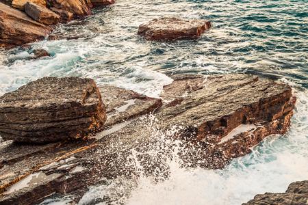 Big stones and waves on sea coast.