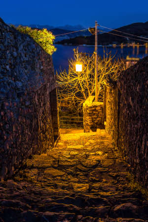 Ancient narrow lane with old lamp in the night.