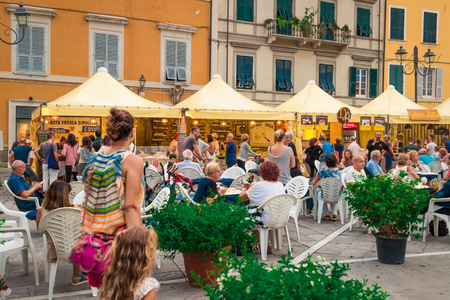 SARZANA, ITALY - AUGUST 10, 2015: Piazza Giacomo Matteotti, Sarzana city, Italy. People eating local food at food fair. Editorial