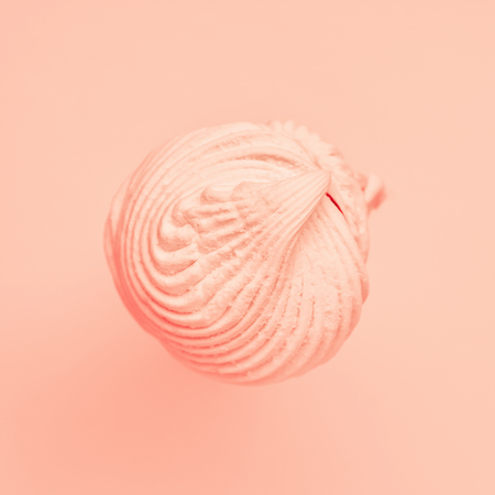 Pink marshmallow flying over pink background. Food concept