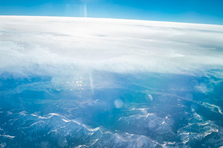 Aerial view above Alpine mountains. Panorama of Alps snowy peaks. Beautiful Alpine mountains landscape.