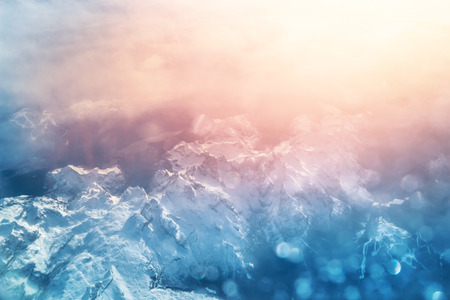 Aerial view above Alpine mountains at sunset. Panorama of Alps snowy peaks. Beautiful Alpine mountains landscape. Standard-Bild