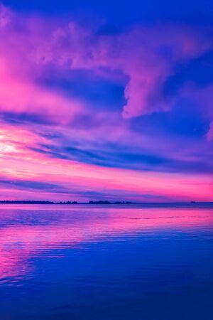 Beautiful pink sunset over river. Nature landscape background Standard-Bild