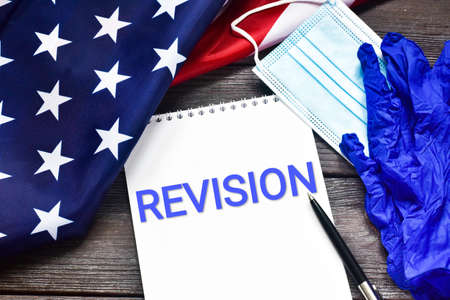 REVISION written text in a notebook against the background of the American flag, medical mask and gloves on a wooden background. Safe revision. Business concept.