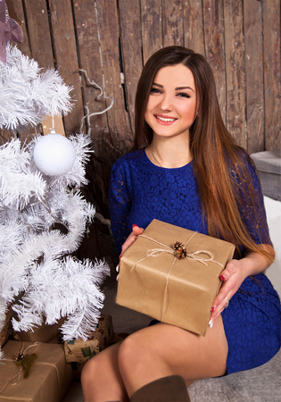 ttractive: Girl in a blue dress holding a gift.