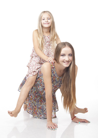 Little girl riding her sister. Isolated on the white background. Stock Photo