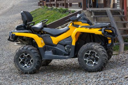 roadless: Yellow all-terrain vehicle. Yellow quadbike. Stock Photo