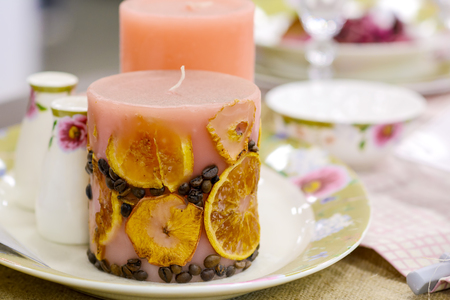 Decorative aroma candle with fruit and coffee on a festive table. Stock Photo