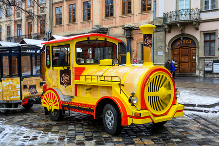 expects: Ukraine, Lviv - December, 15, 2016: Sightseeing road train in the Rynok Square next to Lviv city council expects tourists for a sightseeing tour of the city of Lviv. Editorial
