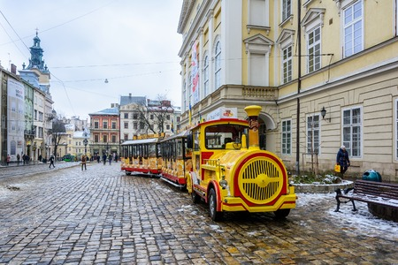 Ukraine, Lviv - December, 15, 2016: Sightseeing road train in the Rynok Square next to Lviv city council expects tourists for a sightseeing tour of the city of Lviv. Editorial
