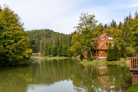 House near the lake in the forest, autumn day.