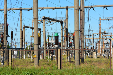 metal grid: High-voltage power lines against the blue sky. Stock Photo