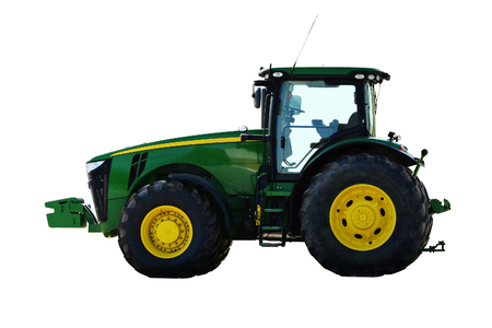 Agricultural machinery tractor. Powerful motor vehicle with large rear wheels, used chiefly on farms for hauling equipment and    trailers. Isolated, white background. Stock Photo