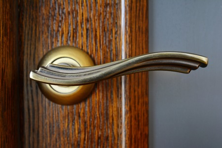 Vintage brass door handle with a latch on a wooden door. Stock Photo