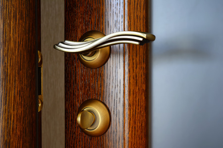 Vintage brass door handle with a latch and a lock on the slightly opened wooden door.