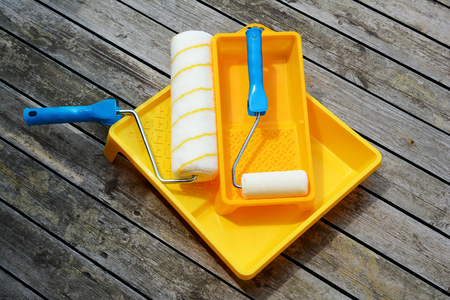 Yellow painting  tray cuvette and paint roller made of synthetic fiber on the surface of wooden slats. Stock Photo
