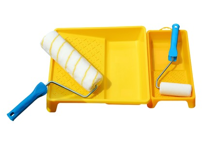 Yellow painting tray and paint roller made of synthetic fiber on the surface of wooden slats. Isolated, white background.