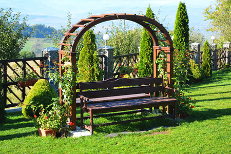 Wooden pergola with white roses, pelargonium and bench in the garden on green lawn.