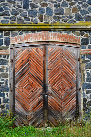 Stone wall of the old mill of granite rocks, old masonry with old wooden gate with iron decoration. Texture, stonework. Stock Photo