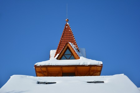 Attic window of triangular shape on snow-covered roof on background of bright blue sky. Sunny winter day. Stock Photo