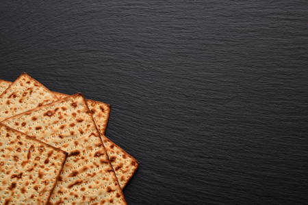 Slices of matzo on plate, board, tray of black slate. Fresh Easter bread made from wheat flour in the form of very thin dry cakes. Stock Photo