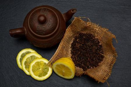 Teapot, half and slices of ripe lemon, dry tea leaves on black slate board, plate or tray.