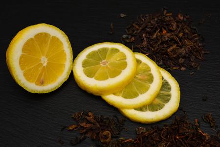 Half and slices of ripe lemon, dry tea leaves on black slate board, plate or tray.