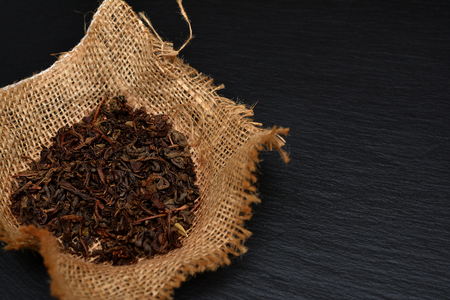 Handful of dry tea leaves on black slate board, plate or tray. Traditional tonic drink.