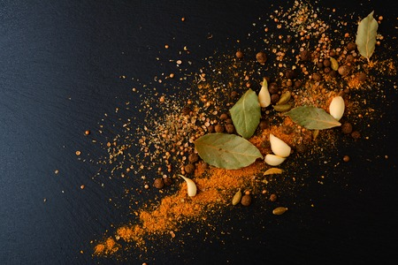 Mix of aromatic spices: black pepper, curry, cardamom, barberry, bay leaf and garlic on black slate board, plate or tray.