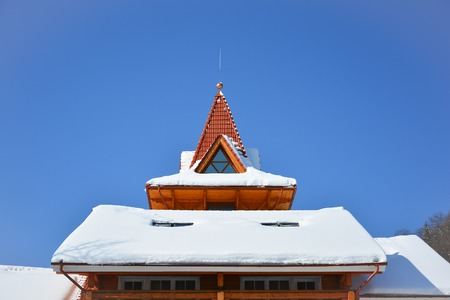 Snow on the roof of wooden house. Attic window of triangular shape on snow-covered roof on background of bright blue sky. Sunny winter day. Stock Photo