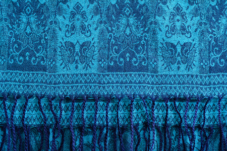 Woolen, cashmere patterned shawl or turquoise scarf with tassels. Blue background. Stock Photo