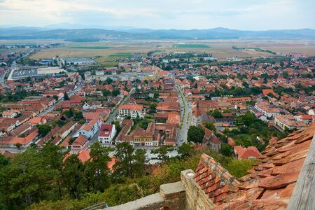 Panorama of the historic city center from the balcony of the medieval fortress Rasnov, Romania. City landscape of the ancient town.