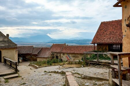 Street of the ancient fortress town. Medieval walled city Rasnov on hill, Romania. Autumn landscape with Medieval fortification Castle Rasnov. Stok Fotoğraf