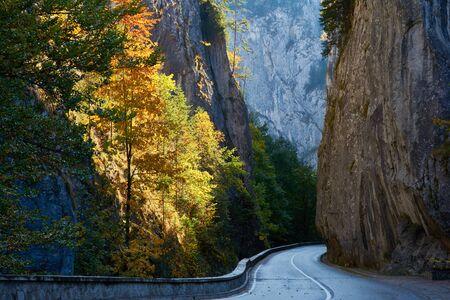 Scenic spot Bicaz Gorge in Carpathian Mountains, Romania. Sunny autumn morning. The road among the rocks. Stok Fotoğraf